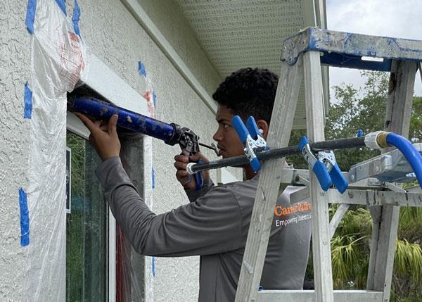Immokalee Student applying Caulking to window