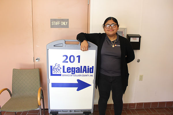 Alondra M. standing next to Legal Aid Service of Collier Sign